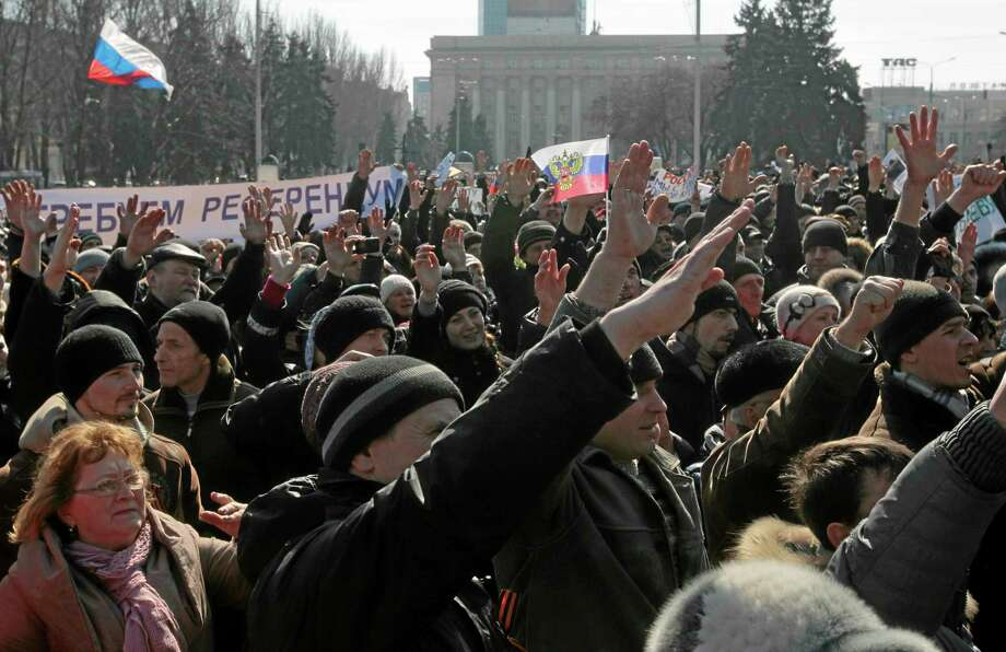 People gesture during a pro Russian rally at a central square in Donetsk, Ukraine, Saturday, March 8, 2014. Pro Russian activists continued to gather on Saturday in the eastern Ukrainian city of Donetsk, as Russia was reported to be reinforcing its military presence in Crimea. Photo: (AP Photo/Sergei Chuzavkov)   / AP