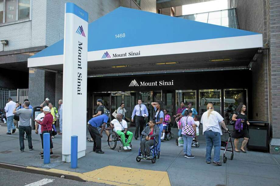 Pedestrians stand outside Mount Sinai Medical Center where a male patient with a high fever and gastrointestinal symptoms was undergoing testing for the Ebola virus following a recent trip to West Africa, Monday, Aug. 4, 2014, in New York. Photo: (AP Photo/John Minchillo) / FR170537 AP