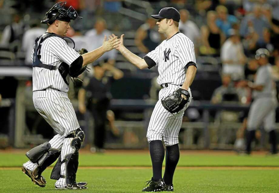 New York Yankees catcher Brian McCann, left, congratulates the Yankees relief pitcher David Robertson after Robertson closed out the Yankees 2-1 victor over the Detroit Tigers in a baseball game at Yankee Stadium in New York, Monday, Aug. 4, 2014.  (AP Photo/Kathy Willens) Photo: AP / AP