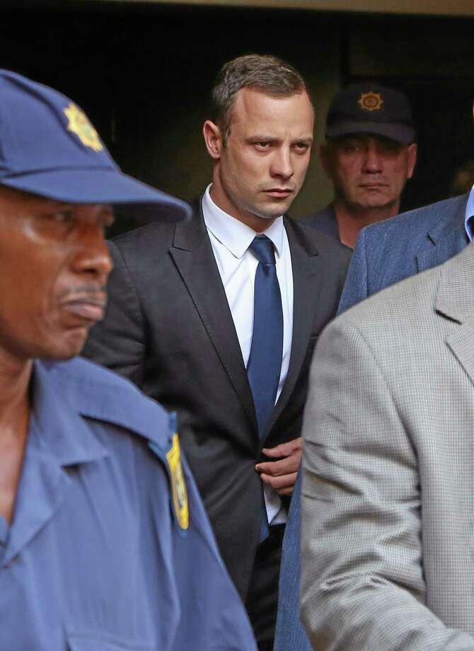 Oscar Pistorius, centre, leaves the high court after the fourth day of his trial in Pretoria, South Africa, Thursday, March 6, 2014. Pistorius is charged with murder in the shooting death of girlfriend Reeva Steenkamp in the pre-dawn hours of Valentine's Day 2013. (AP Photo/Schalk van Zuydam) Photo: AP / AP