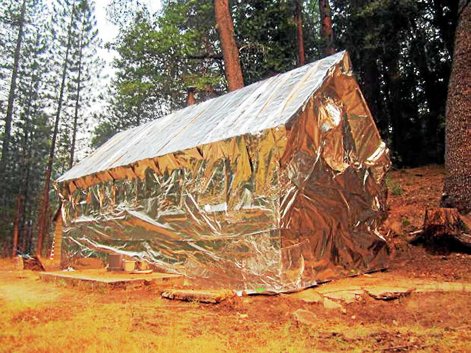 In this Aug. 2, 2014 photo provided by Bob Grate, firefighters from the Black Eagle II Hotshot crew have wrapped a historic cabin with radiant and convective heat resistant materials as protection against the French Fire in the Sierra National Forest near North Fork, Calif. Humid conditions gave crews hope in their battle against two wildfires in Northern California that have scorched more than 100 square miles and are menacing a small town. Photo: AP Photo/Bob Crate  / Bob Crate