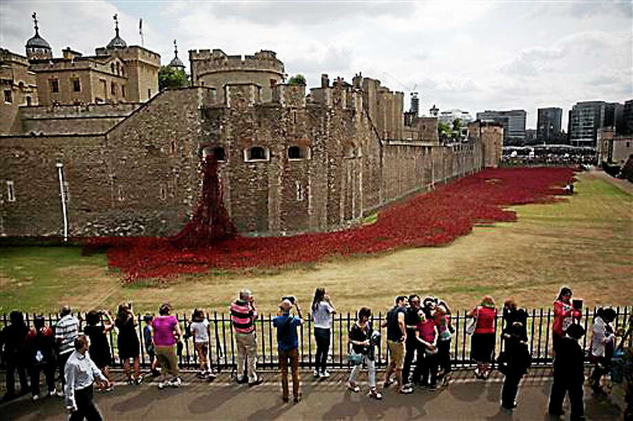 A group of people pose for a selfie backdropped by the ceramic poppy art installation by artist Paul Cummins entitled 'Blood Swept Lands and Seas of Red' after its official unveiling in the dry moat of the Tower of London in London, Tuesday, Aug. 5, 2014.  Britain's Prince William, his wife Kate Duchess of Cambridge and his brother Prince Harry visited the work in progress installation Tuesday to mark the centenary of World War I. The installation currently consists of about 120,000 ceramic poppies and will finish with 888,246 poppies, with the final poppy being placed on Armistice Day on November 11.  Each poppy represents a British and Commonwealth military fatality from World War I.  (AP Photo/Matt Dunham) Photo: AP / AP