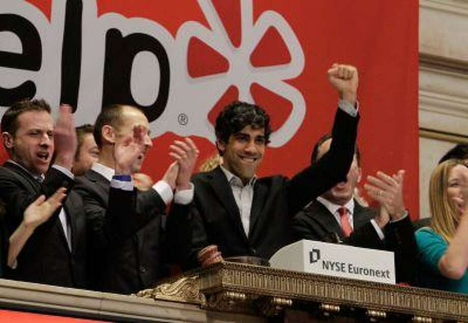 Jeremy Stoppelman, right center, Yelp co-founder and CEO, salutes during opening bell ceremonies of the New York Stock Exchange in March 2012. (Associated Press/Richard Drew) Photo: ASSOCIATED PRESS / AP2012