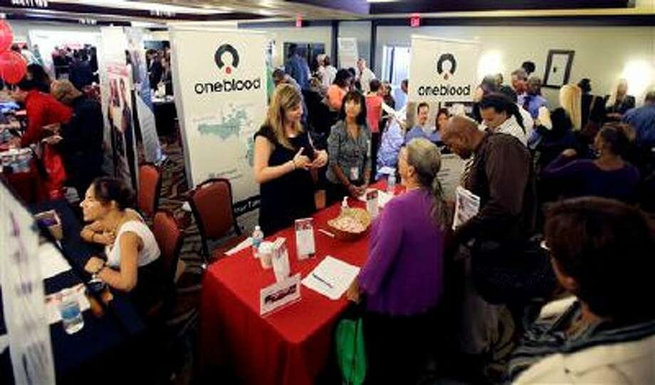 In this Wednesday, Aug. 14, 2013 photo, job seekers check out companies offering more than 2,000 job opportunities at a job fair in Miami Lakes, Fla. The number of people seeking U.S. unemployment benefits rose 13,000 the week of Aug. 12, to a seasonally adjusted 336,000, but the level remains consistent with solid job gains, according to information released by the Labor Department, Thursday, Aug. 22, 2013. (AP Photo/Alan Diaz) Photo: AP / AP