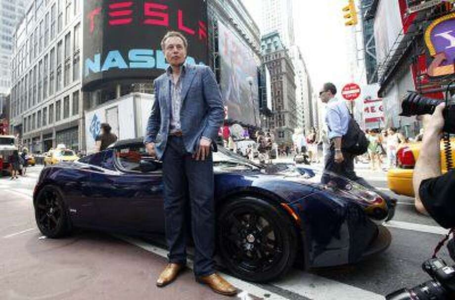 """Elon Musk, CEO of Tesla Motors, poses with a Tesla car in front of Nasdaq following the electric automaker?s initial public offering, Tuesday, June, 29, 2010, in New York. The company plans to trade on the Nasdaq stock exchange under the ticker """"TSLA."""" (AP Photo/Mark Lennihan) Photo: ASSOCIATED PRESS / AP2010"""