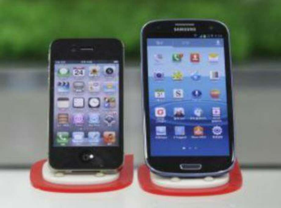 Apple iPhone, left, and Samsung Galaxy S III smartphones. (AP Photo/Ahn Young-Joon) Photo: AP / AP