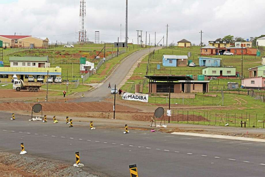 A banner reading 'Madiba', next to the main road leading past former president Nelson Mandela's home, as construction still continues in Qunu, South Africa, Monday, Dec. 9, 2013. The home  where Nelson Mandela grew up had mud walls, a grass roof, and a floor polished smooth with cow dung. That was in the 1920s. When people flood Mandela's village on Sunday for the former president's burial, they will be in a place that _ except for a gleaming new highway and a strong cellphone network lags decades behind the  developed world. (AP Photo/Schalk van Zuydam) Photo: AP / AP