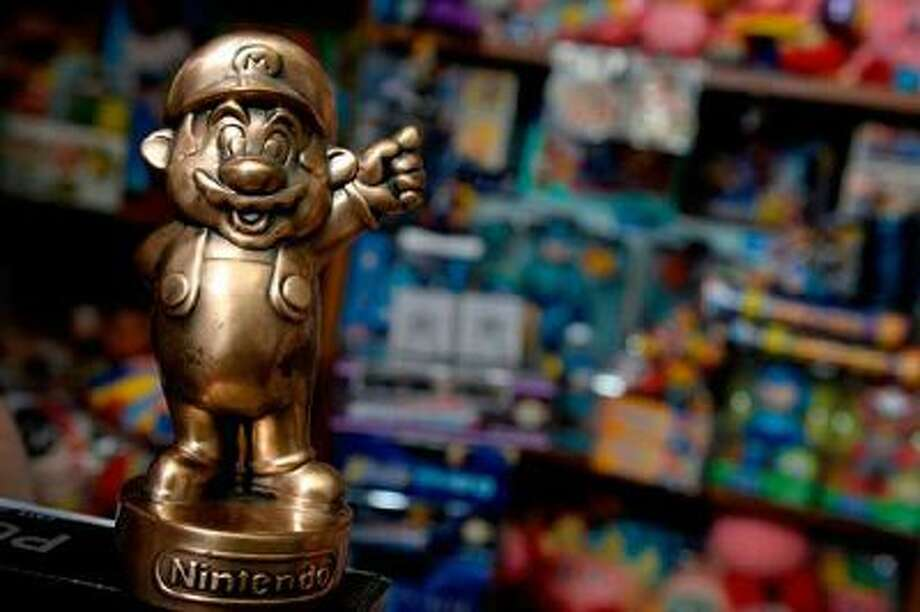 """LITTLETON, CO. - FEBRUARY 25:  Brett Martin has a """"Nintendo Oscar"""" in his """"Video Game Memorabilia Museum,"""" at his home in Littleton, CO February 25, 2014. His collection has been recognized by the Guinness Book of World Records as the Largest Collection of Video Game Memorabilia with 8030 pieces. Martin says that Nintendo gave the bronze statues to employees. (Photo By Craig F. Walker / The Denver Post) / Copyright - 2013 The Denver Post, MediaNews Group."""