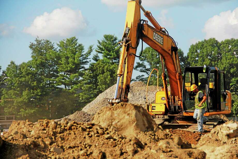 A construction worker steps out of an excavator at the Torrington High School athletic field complex Monday. Construction on the site is scheduled to be completed in the fall. Photo: Esteban L. Hernandez — The Register Citizen