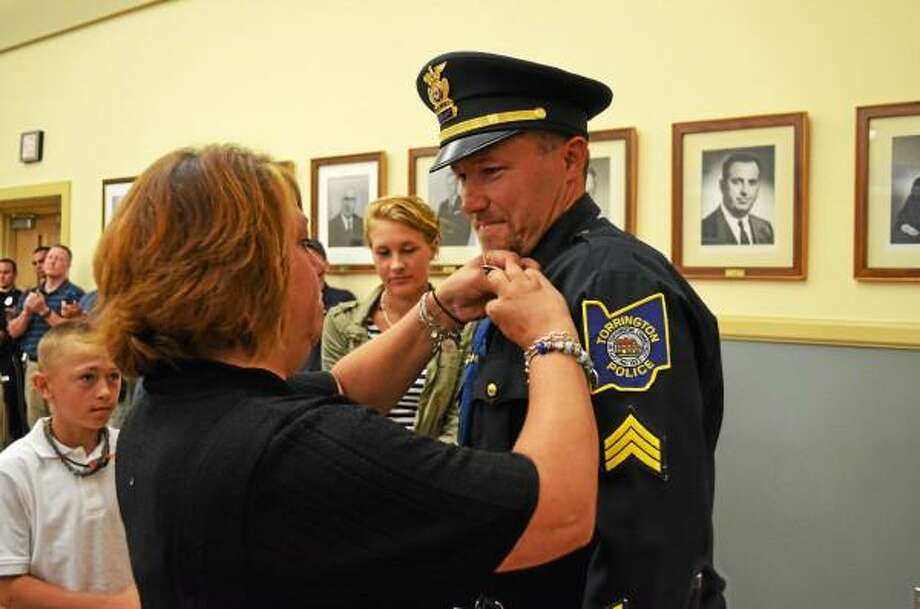 Sgt. Dustin Baldis watches as his wife, Tracy, places a new badge on his uniform during a promotion ceremony at City Hall Auditorium on Wednesday. ESTEBAN L. HERNANDEZ - REGISTER CITIZEN