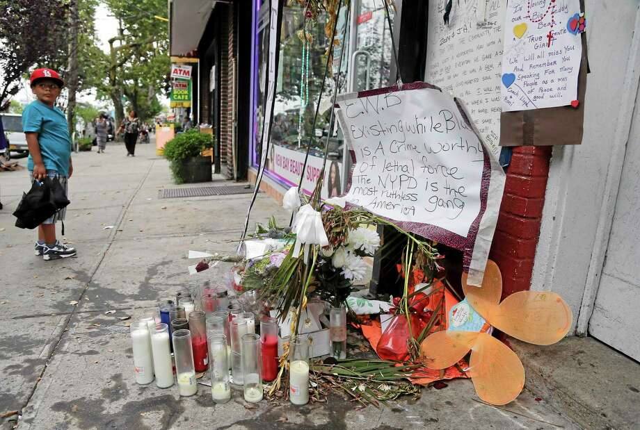 A young boy stops as he passes a makeshift memorial for Eric Garner, Friday, Aug. 1, 2014, in the Staten Island borough of New York. Garner was put in a chokehold while being arrested at the site last month for selling untaxed loose cigarettes. On Friday, the medical examiner ruled Garner's death to be a homicide caused by a police chokehold. (AP Photo/Julie Jacobson) Photo: AP / AP