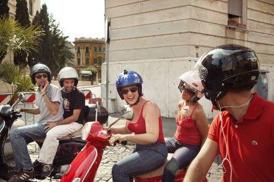 From left, Scooteroma's Giovanni Nerone, Fabio Magneli, Scooteroma's Annie Ojile Nerone and Fatima Giorgili take a Vespa tour of Rome on July 14. Illustrates TRAVEL-ROME (category t), by Kelly DiNardo, special to The Washington Post. Moved Tuesday, August 6, 2013. (MUST CREDIT: Photo by Alessandro Penso via OnOff Picture For The Washington Post). Photo: The Washington Post / THE WASHINGTON POST