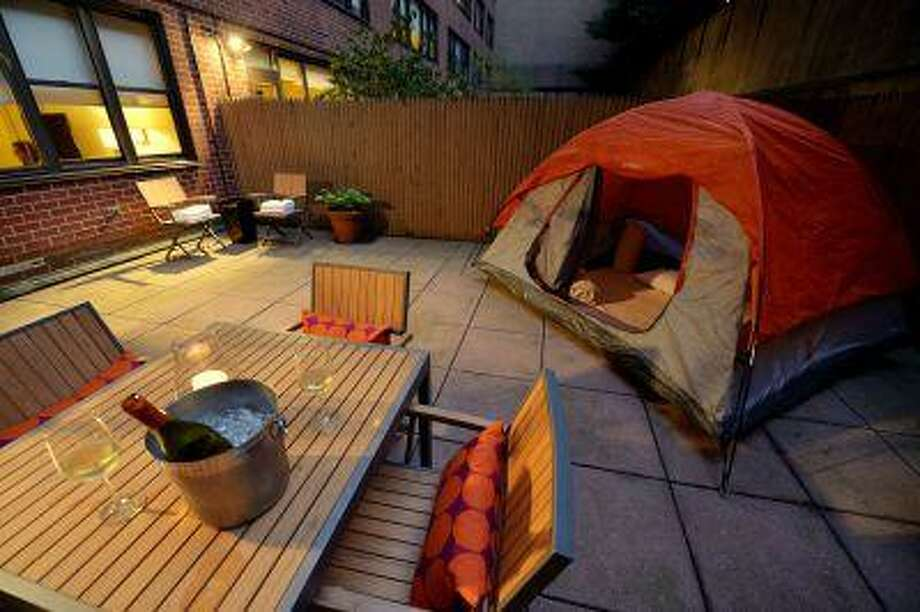 """TO GO WITH AFP STORY BY PRUNE PERROMAT A tent on a brick patio of a ground floor room in the Affinia Gardens Hotel July 15, 2013 in New York. Affinia Gardens, located on the Upper East Side of Manhattan, provides guests with the opportunity to """"camp"""" outside with their own backyard first-floor Private Garden Terrace Suites. The suites feature more than 600 square feet (55.7 square meters) of space, including brick patio, table with four chairs, a fence includes such amenities and services as tents and flashlights, S'mores-making kit and Yoga Stay Fit Kit. AFP PHOTO/Stan HONDA Photo: AFP / AFP ImageForum"""