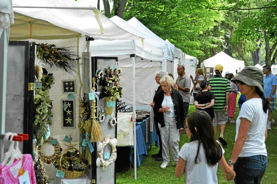 Locals survey the diverse goods at the 55th annual arts and crafts fair on the green. Photo: Ryan Flynn — Register Citizen
