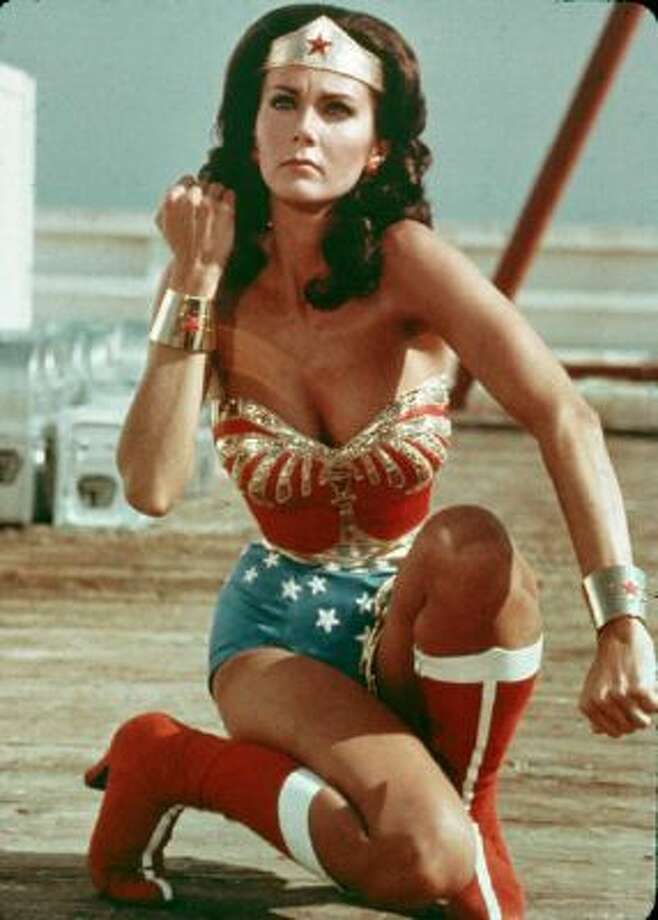 American actor Lynda Carter kneels on the ground and bears her forearm in a still from the television series Wonder Woman. Photo: Getty Images / Hulton Archive