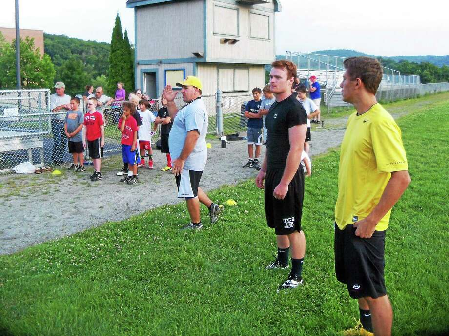 Peter Wallace - Register Citizen Gilbert/Northwestern alumni players Nick Pedrolini, right and Johnny Lippincott join Head Coach Scott Salius and a few of the campers at the sledge-pull finish line. Photo: Journal Register Co.