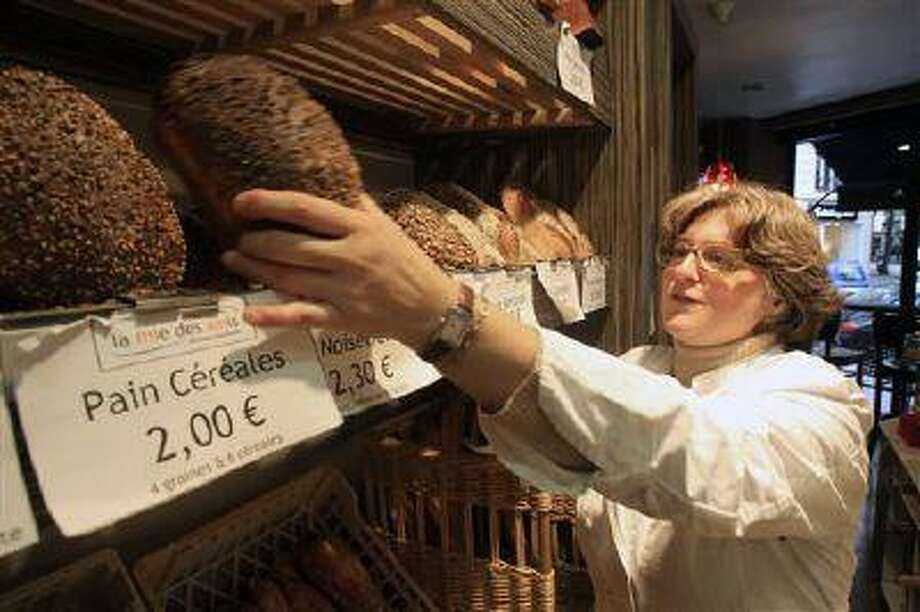Estelle Levy sets up loaves of bread in her bakery in Paris. France, the country that gave us the words restaurant, bistro and cuisine, is changing how it eats. (Remy de la Mauviniere/AP) Photo: AP / AP