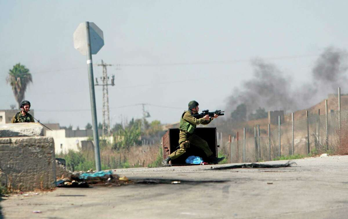 An Israeli soldier fires towards Palestinian protesters, following a protest against the war in the Gaza Strip, during clashes near the West Bank town of Tulkarem on Friday, Aug. 1, 2014. A Palestinian man was shot and later died during clashes with Israeli troops near Tulkarem, Palestinian security sources said. (AP Photo/Mohammed Ballas)
