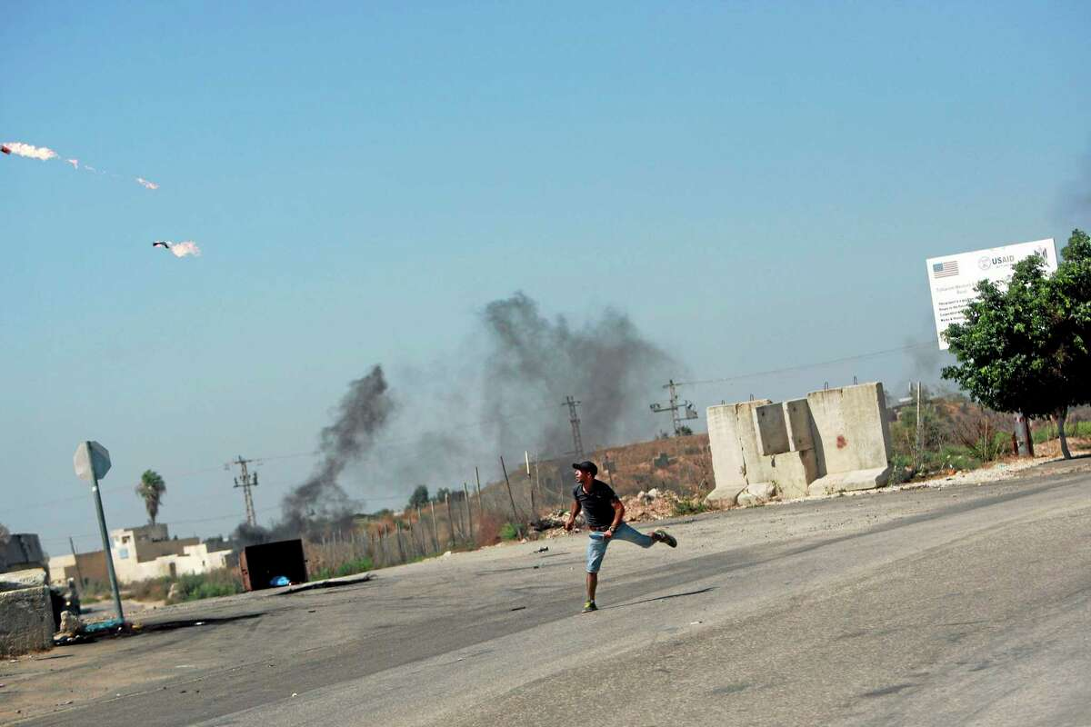 A Palestinian protester throws a Molotov cocktail towards Israeli troops, following a protest against the war in the Gaza Strip, during clashes near the West Bank town of Tulkarem on Friday, Aug. 1, 2014. A Palestinian man was shot and later died during clashes with Israeli troops near Tulkarem, Palestinian security sources said. (AP Photo/Mohammed Ballas)