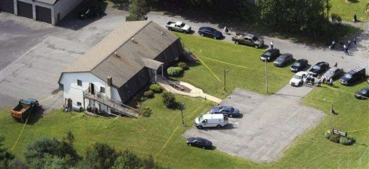 This aerial photo, police tape surrounds the Ross Township municipal building on Tuesday, Aug. 6, 2013. A man who fatally shot a township official and two others during a municipal meeting in northeastern Pennsylvania was about to fire more rounds from his handgun when he was wrestled to the ground, possibly saving more bloodshed, authorities said Tuesday. About 15 to 18 residents and town officials were at the Ross Township meeting Monday night when the gunfire erupted, according to Pennsylvania State Police. The gunman, 59-year-old Rockne Newell, who had been involved in a long-running dispute with the township over a dilapidated property, was tackled to the ground by two people and was shot with his own gun, authorities said. He was treated at a hospital for a gunshot wound to the leg and was arraigned Tuesday on homicide charges and other counts. (AP Photo/Pocono Record, David Kidwell)