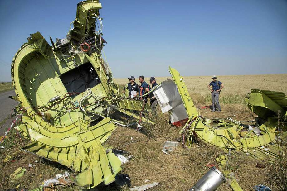 Australian and Dutch investigators examine pieces of the Malaysia Airlines Flight 17 plane crash in the village of Hrabove, Donetsk region, eastern Ukraine Friday, Aug. 1, 2014. The investigators from the Netherlands and Australia plus officials with the Organization for Security and Cooperation in Europe traveled from the rebel-held city of Donetsk in 15 cars and a bus to the crash site outside the village of Hrabove. Then they started setting up a base to work from at a chicken farm. (AP Photo/Dmitry Lovetsky) Photo: AP / AP
