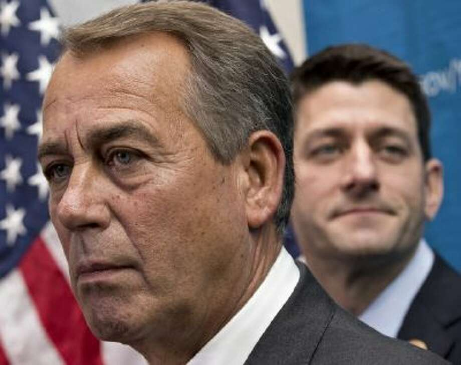 House Speaker John Boehner of Ohio, left, joined by House Budget Committee Chairman Rep. Paul Ryan, R-Wis., takes reporters' questions, on Capitol Hill in Washington, on Dec. 11.
