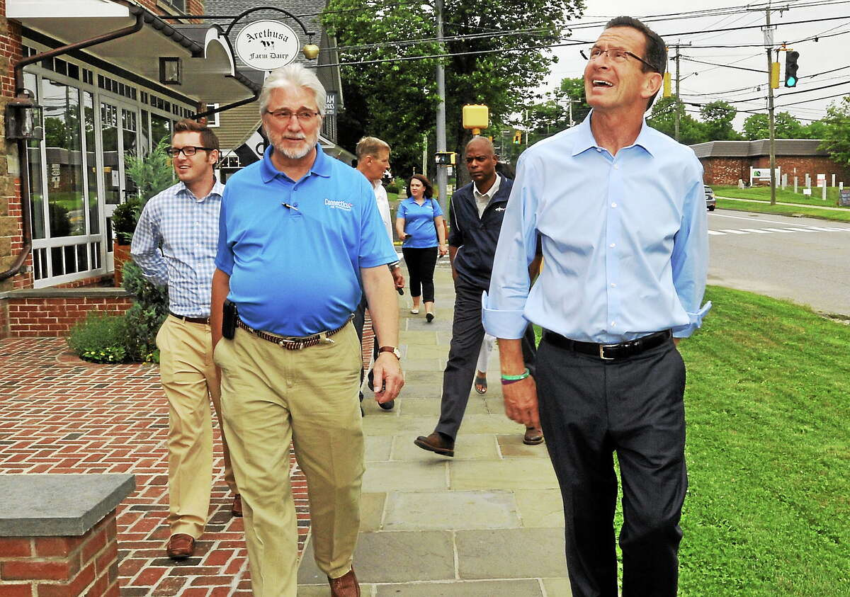 Gov. Dannel Malloy, right, walks along Bantam Road in front of Arethusa Farm Dairy in Litchfield Friday. Malloy made three stops in Litchfield County to highlight popular tourism destinations the region has to offer.