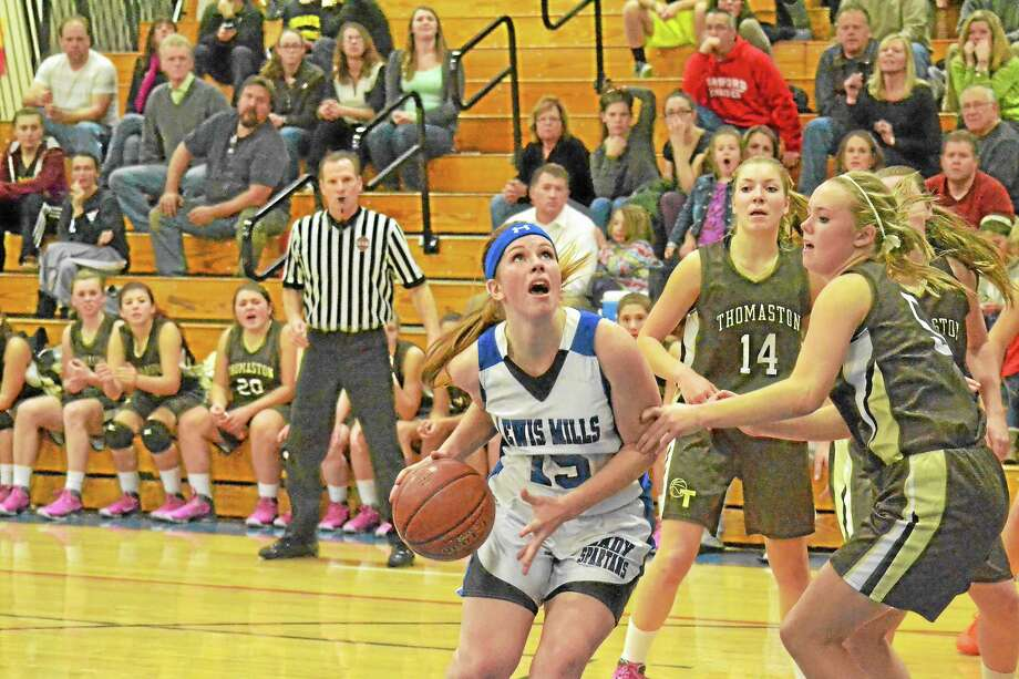 Lewis Mills' Teagan Dunn drives past Thomaston's Abby Hurlbert during the Spartans 46-42 win over Thomaston. Dunn finished with 18 points and 20 rebounds. Photo: Pete Paguaga — Register Citizen