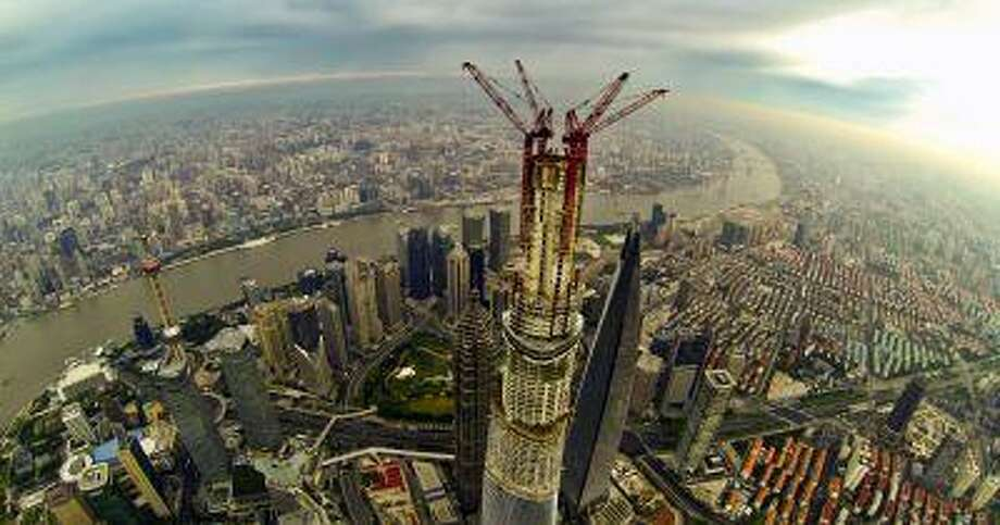 This picture taken on August 4, 2013 shows a general view of the under-construction Shanghai Tower (C) and the 492m Shanghai World Financial Center (R), the 421m Jin Mao Tower (L) in Shanghai. Work on the main structure of the world's second tallest skyscraper was completed on August 3 as a crane placed a steel beam 1,900 feet above the ground, as the building formally overtook Taiwan's 509 meter tall Taipei 101 building to become the tallest tower in Asia. CHINA OUT AFP PHOTO (Photo credit should read ) edit Photo: AFP/Getty Images / 2013 AFP