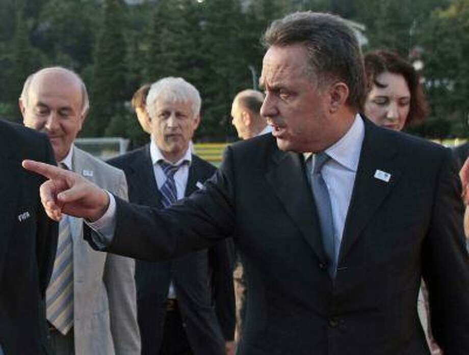 FILE - In this file photo taken on Wednesday, Aug. 18, 2010, Russian Sports Minister Vitaly Mutko, foreground, points as he visits a central soccer stadium in the Black Sea resort of Sochi, southern Russia. Mutko said Thursday Aug 12013 that a new law cracking down on gay rights activism will be enforced during the 2014 Olympics in Sochi. (AP Photo/Igor Yakunin, file) Photo: AP / AP