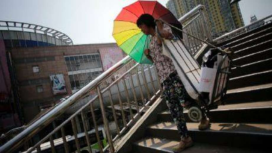 A woman courier with a parasol walks down a pedestrian bridge in the hot summer sun in Shanghai, China, Thursday, Aug. 1, 2013. (Eugene Hoshiko/AP)
