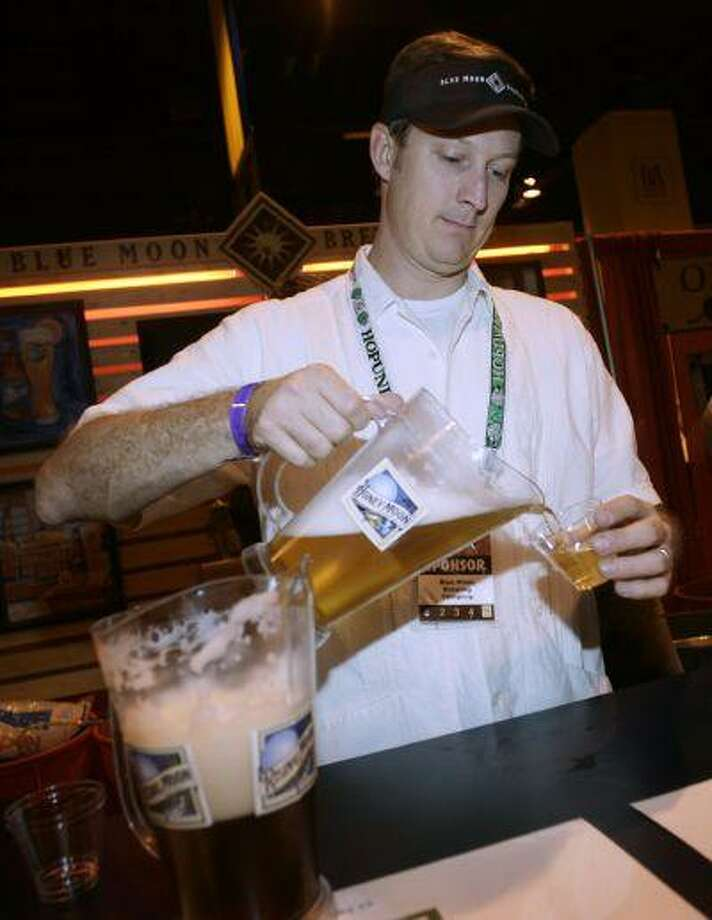 John Wilhelm of Denver pours a sample of brew from Blue Moon Brewing Company for an attendee at the Great American Beer Festival in the Colorado Convention Center in downtown Denver on Thursday, Oct. 11, 2007. The festival, in its 26th year, will offer festival goers more than 1,800 beers on tap from 408 U.S. breweries during the three-day event. (AP Photo/David Zalubowski) Photo: ASSOCIATED PRESS / AP2007