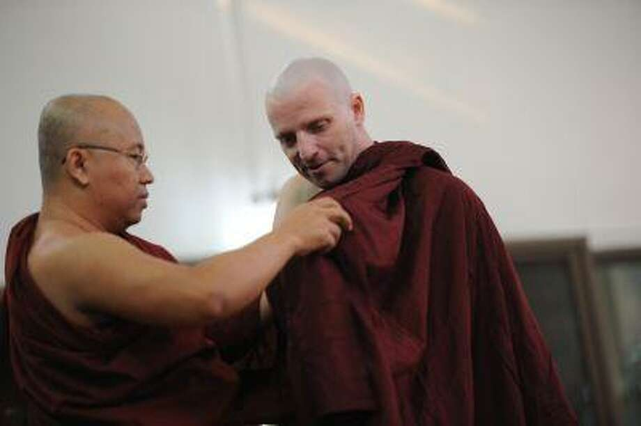 British art historian, Rupert Richard Arrowsmith, right, has his hair shaved before he enters monastic life at a monastery on the outskirts of Yangon Feb. 23. Photo: AFP / AFP ImageForum