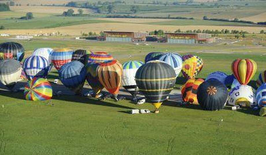"""Hot air-balloons are about to fly over Chambley-Bussieres, eastern France, before the world record attempt of the biggest line with 391 balloons on August 1, 2013 as part of the yearly event """"Lorraine Mondial Air Ballons"""", an international air-balloon meeting. Photo: AFP/Getty Images / 2013 AFP"""