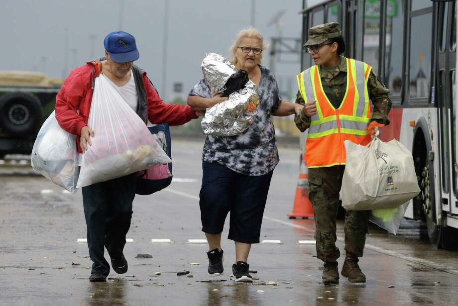 A National Guard member helps people Sunday as they walk along Interstate 45 South near Edgebrook to board Metro buses to be taken to a shelter at the George R. Brown Convention Center. Photo: Melissa Phillip, Staff / Houston Chronicle 2017