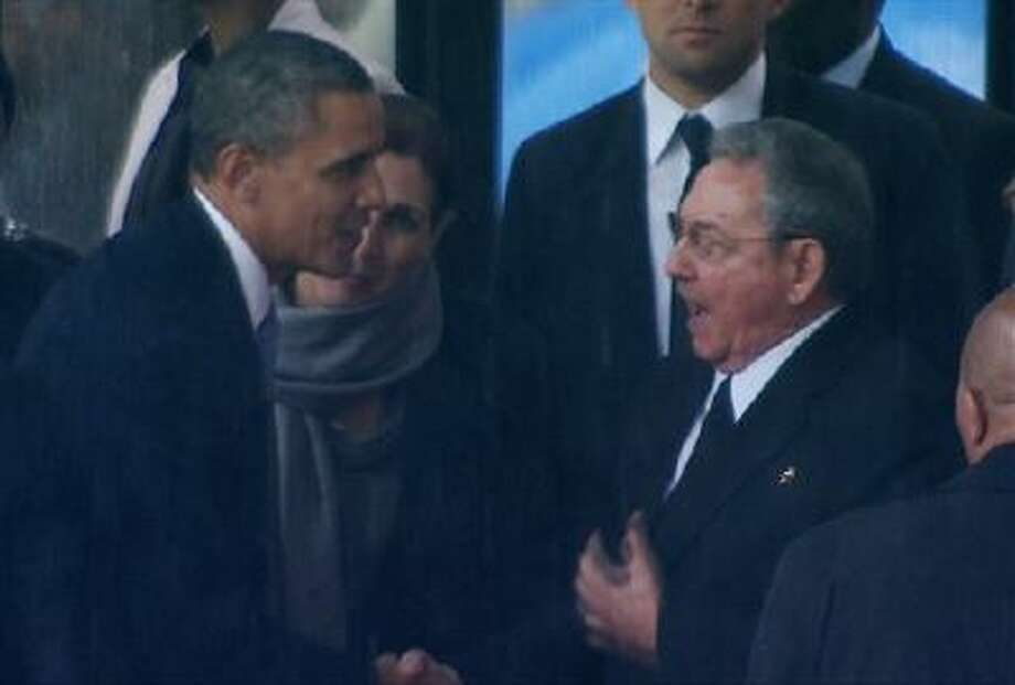 In this image from TV, US President Barack Obama shakes hands Tuesday with Cuban President Raul Castro in Soweto, South Africa, in the rain for a memorial service for former South African President Nelson Mandela. Photo: AP / SABC