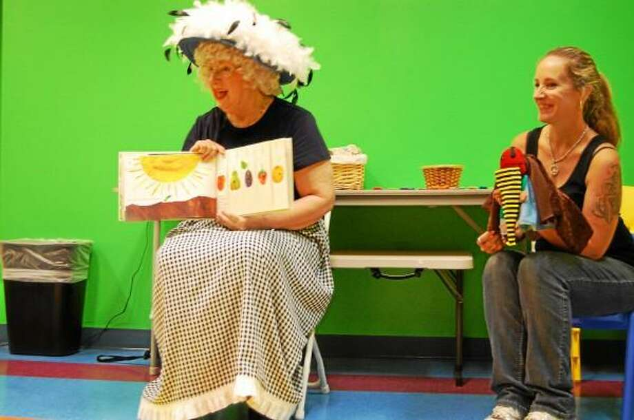 Pamela Meier, Granny Goosefeathers reads The Very Hungry Caterpillar to children at KidsPlay Children's Museum Friday afternoon while her daughter and assistant Diane Audet holds the caterpillar that the kids fed until it turned into a butterfly. Jenny Golfin - Register Citizen