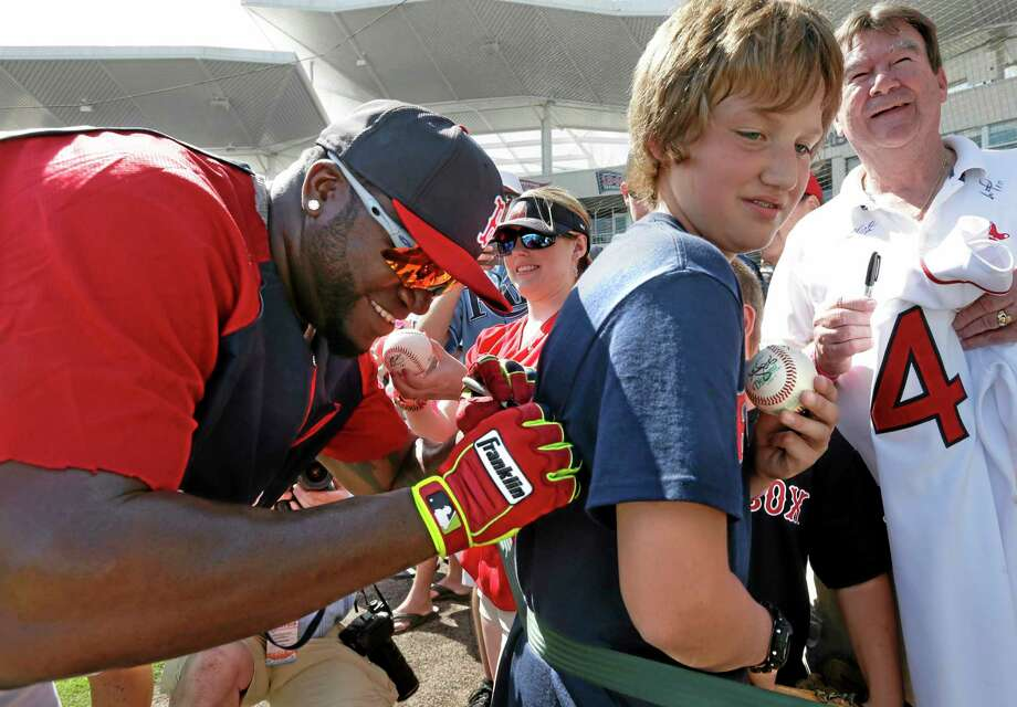 Red Sox designated hitter David Ortiz signs an autograph on a shirt for a fan before Boston's spring training game against the Tampa Bay Rays on Tuesday in Fort Myers, Fla. The Rays won 8-0. Photo: Steven Senne — The Associated Press  / AP