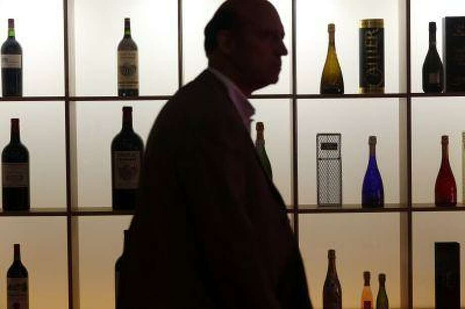 A man walks in front of a wall of wine bottles displayed during the Vinexpo trade fair in Bordeaux, southwestern France, on June 17, 2013. Photo: AFP/Getty Images / 2013 AFP