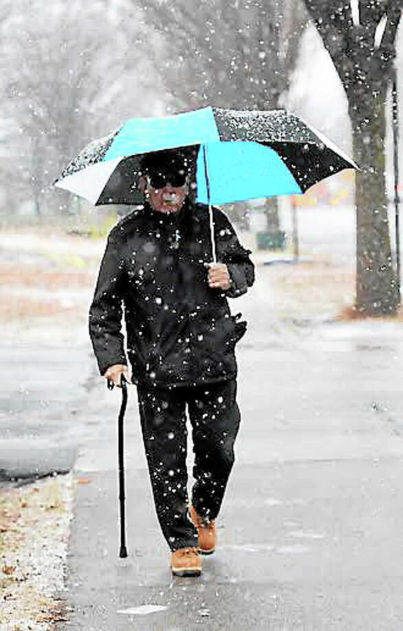 Louis Torres of New Haven, 69, walks through snowfall  on Grand Ave. in New Haven Tuesday morning December 10, 2013. (Peter Hvizdak-New Haven Register) Photo: Journal Register Co. / ©Peter Hvizdak /  New Haven Register