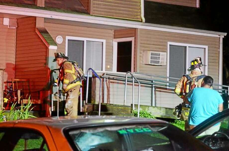 Torrington firefighters check apartments in the Woodland Hills apartment complex in Torrington Sunday night after a kitchen fire was extinguished in the building at 330 Highland Ave. John Berry - Register Citizen
