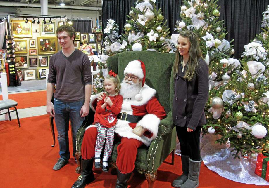 """In Nov. 29, 2013 photo taken from video, siblings Maddie, 5, Mackenzie, 15, and Caleb Bunn, 18, from Rocky Mount, N.C., pose for a photo with """"Santa"""" Cliff Snider at the Christmas Carousel show in Raleigh, N.C. Caleb is graduating from high school this year, and his mother says he agreed to pose for one last photo with Santa. (AP Photo/Allen G. Breed) Photo: AP / AP"""