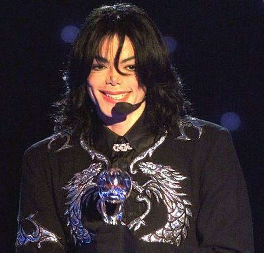 """In this May 10, 2000 photo, pop star Michael Jackson gestures to spectators as he holds the """"Millennium Award"""" which was awarded to him at the 2000 World Music Awards ceremony in Monaco. (AP Photo/Lionel Cironneau, file) Photo: AP / AP"""