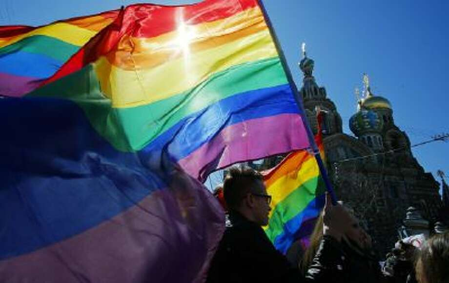 In this May 1, 2013, file photo, gay rights activists carry rainbow flags as they march during a May Day rally in St. Petersburg, Russia.