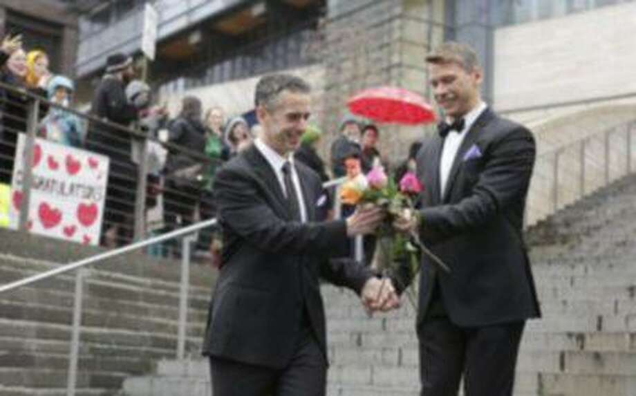 Seattle gay-rights advocate and journalist Dan Savage (L) and Terry Miller sort through roses on the steps of City Hall after getting married at Seattle City Hall in Seattle, Washington, in this Dec. 9 photo.