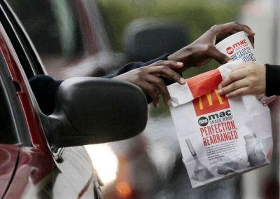 In this Jan. 22, 2010 file photo, a customer grabs lunch at a McDonalds drive-through in Chicago. Fast-food chains such as McDonald's, Burger King and Wendy's are trumpeting pricier, premium offerings to shed their image as purveyors of greasy junk food and convince customers to spend a few extra bucks. .(AP Photo/M. Spencer Green, File) Photo: ASSOCIATED PRESS / A2010
