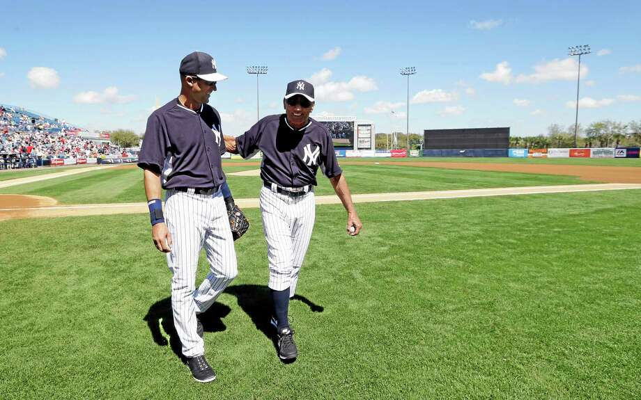 Former New York Jets quarterback Joe Namath walks off the field with Yankees shortstop Derek Jeter Monday in Tampa, Fla. Photo: Charlie Neibergall — The Associated Press  / AP