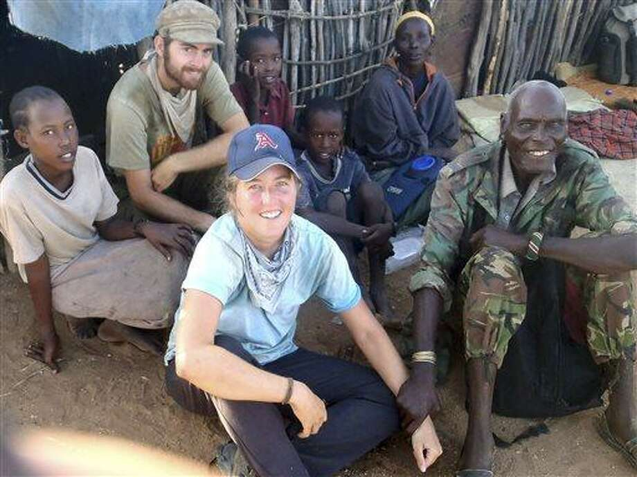 """In this May 18, 2013 photo provided by Amy Russell, of Manchester, Conn., Russell, left, and walking partner Aaron Tharp, rear second from left, pose for a photo in northern Kenya with a guide, right, they called """"Grandpa"""" and the family they stayed with in a small village that night, as they traveled through lion territory during a trek across Africa.  Due to health problems and political unrest in her planned destination of Egypt, Russell, founder of the charity Walking4Water, ended her trek across Africa, six months and 2,000 miles earlier than planned. (AP Photo/Amy Russell) Photo: AP / Amy Russell"""