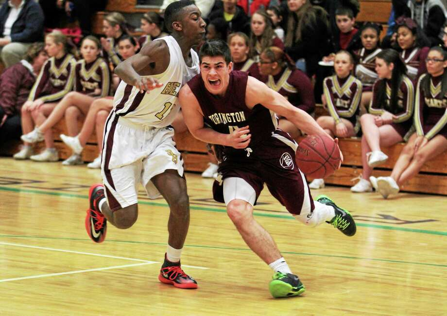 Torrington's John McCarthy drives to the basket while contested by a Sacred Heart defender. Photo: Marianne Killackey — Special To Register Citizen  / 2013