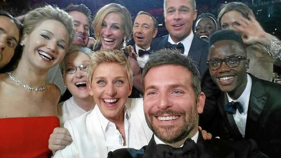 """This image released by Ellen DeGeneres shows actors front row from left, Jared Leto, Jennifer Lawrence, Meryl Streep, Ellen DeGeneres, Bradley Cooper, Peter Nyongío Jr., and, second row, from left, Channing Tatum, Julia Roberts, Kevin Spacey, Brad Pitt, Lupita Nyongío and Angelina Jolie as they pose for a """"selfie"""" portrait on a cell phone during the Oscars at the Dolby Theatre on Sunday, March 2, 2014, in Los Angeles. (AP Photo/Ellen DeGeneres) Photo: AP / Ellen DeGeneres"""